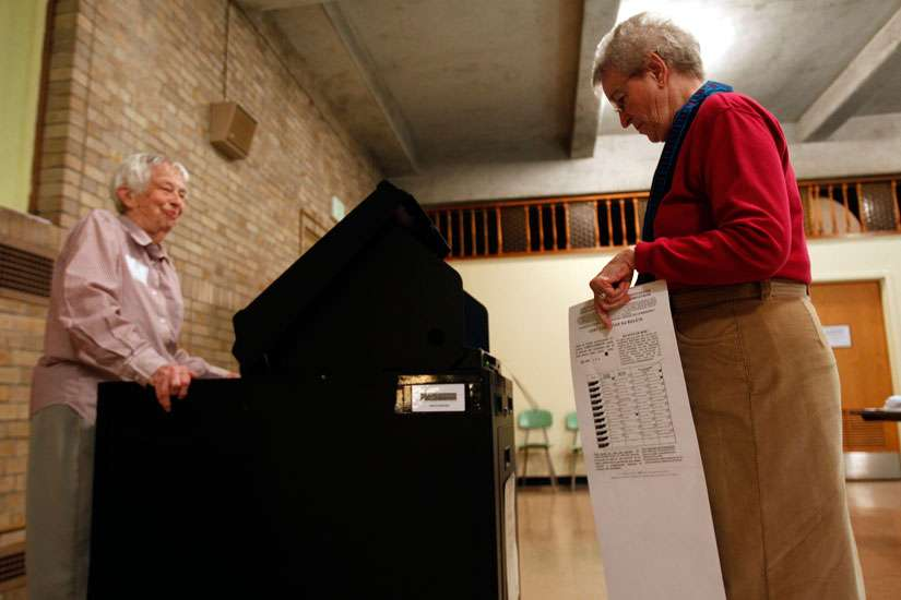 A Maryknoll sister casts her vote at a polling station inside her religious community's auditorium in 2010 in Ossining, N.Y.