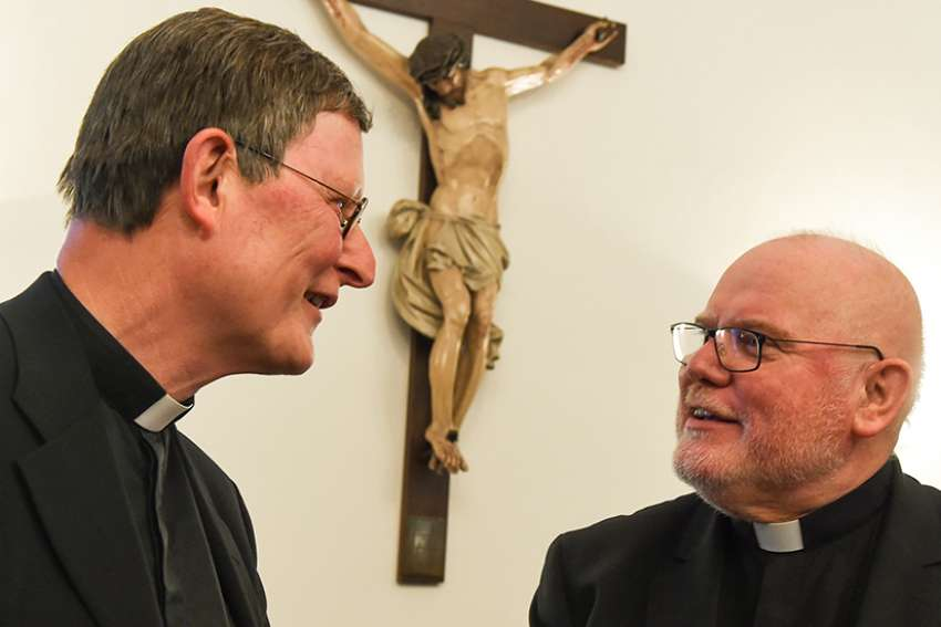 Cardinal Rainer Maria Woelki of Cologne, Germany, talks with Cardinal Reinhard Marx of Munich and Freising, president of the German bishops' conference, at the opening of the bishops' plenary assembly in Fulda, Germany, Sept. 19, 2016. Cardinals Woelki and Marx disagree about whether the bishops' conference has the authority to develop its own guidelines about non-Catholic spouses receiving Communion.