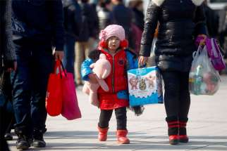 A young girl carrying a stuffed toy holds on to her mother's hand in 2013 as they walk outside the train station in Beijing. China's Communist Party leaders announced they would change the nation's one-child policy, which most strictly applied to Han Chinese living in urban areas of the country.