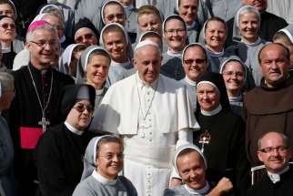 Pope Francis poses with clergy and women religious during his general audience in St. Peter's Square at the Vatican Oct. 7, 2015. The Pope has appointed a panel of six women and six men to study women deacons