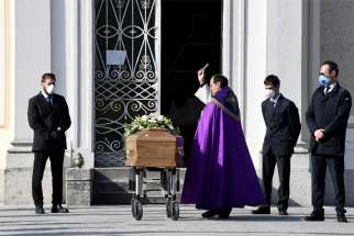 A priest blesses the coffin of a woman who died from COVID-19 in Seriate, Italy, March 28, 2020. The Italian bishops' conference is in discussion with Italy's Ministry of Internal Affairs about a resumption of public Masses, and especially of funerals.
