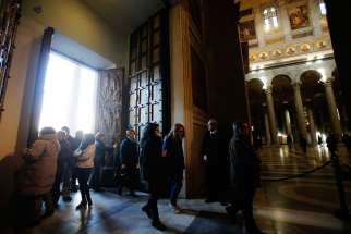 Pilgrims pass through the Holy Door of the Basilica of St. Paul Outside the Walls in Rome Dec. 13. U.S. Cardinal James M. Harvey, archpriest of the basilica, opened the Holy Door Dec. 13 as part of the Jubilee Year of Mercy.