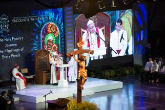 Pope Francis and Cardinal Luis Antonio Tagle of Manila, Philippines, are seen on a big screen during a meeting with families at the Mall of Asia Arena in Pasay City, Philippines, Jan. 16.