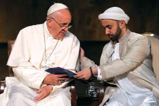 Pope Francis accepts a program from Iman Khalid Latif during an interreligious gathering in New York in 2015.