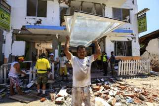 Residents recover some of their belongings April 25 from debris of a destroyed building in Canoa, Ecuador. Catholic agencies will begin building temporary shelters for thousands of families displaced by the April 16 magnitude-7.8 earthquake, the country's worst natural disaster in nearly seven decades.
