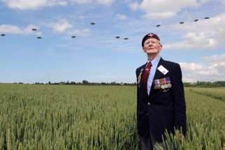 British World War II veteran Frederick Glover poses for a photo June 5 as soldiers parachute down during D-Day commemoration ceremonies in Ranville, France. About 18 heads of state were to attend ceremonies bringing together 3,000 veterans along France's Normandy coast where Allied forces landed on June 6 , 1944 in a seaborne invasion that sped up the defeat of Nazi Germany in World War II.