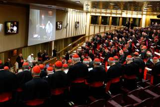 The German, French and Swiss bishops' conference presidents prepared for the upcoming Synod of Bishops by listening to theologians, scholars and lawyers. In this photo, Pope Francis, cardinals and cardinals-designate pray before a meeting in the synod hall at the Vatican Feb. 12, 2015.