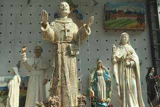 Statues of Pope Francis and his namesake, St. Francis, fill the windows of souvenir stores in Assisi.