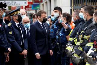 French President Emmanuel Macron talks with first responders outside Notre Dame Basilica in Nice Oct. 29, 2020, after at least three people were killed in a series of stabbings before Mass. France raised its alert level to maximum after the attack.