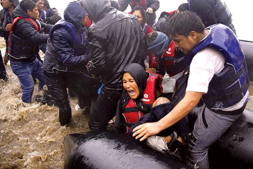 An Afghan mother holds her baby as she struggles to disembark a raft during a rainstorm in Lesbos, Greece, Oct. 23. The Canadian bishops have called for urgent action to aid refugees.