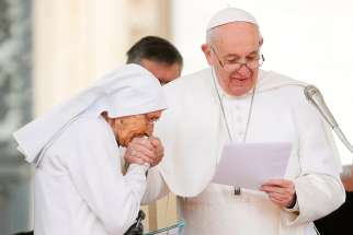 Sister Maria Concetta Esu, an 85-year-old Daughter of St. Joseph, kisses the hand of Pope Francis after the pontiff awarded her the Pro Ecclesia et Pontifice Cross during his general audience in St. Peter's Square at the Vatican March 27, 2019.