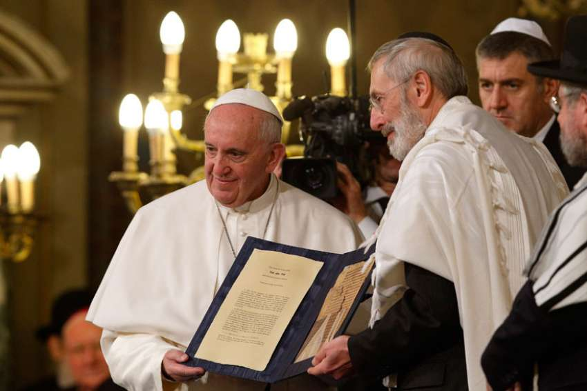 Pope Francis and Rabbi Riccardo Di Segni, the chief rabbi of Rome, hold a codex containing five pages of Jewish biblical commentary during the pope's visit to the main synagogue in Rome Jan. 17, 2016.