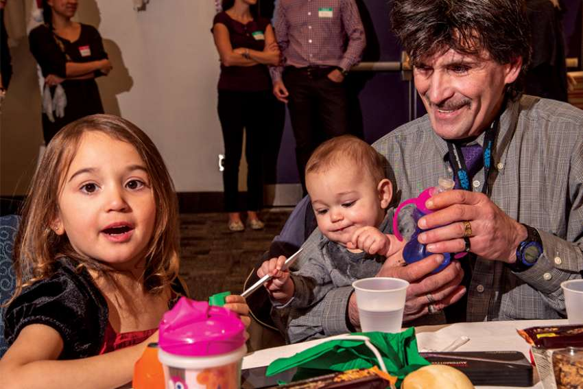 Ray Taylor, holding his son Matthew, along with his daughter Sarah, were full of anticipation for the Christmas dinner at the annual Good Shepherd event at the Hamilton Convention Centre.