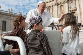 Children join Pope Francis in the popemobile during his general audience in St. Peter's Square at the Vatican Sept. 25, 2019.