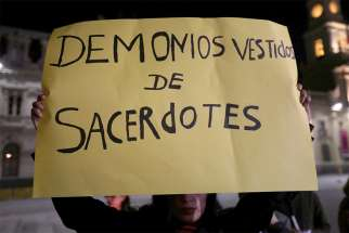"A woman holds a banner that reads ""Devils Dressed as Priests"" during an Aug. 20 vigil to protest against sexual abuse in the Chilean Catholic church outside the Santiago cathedral."