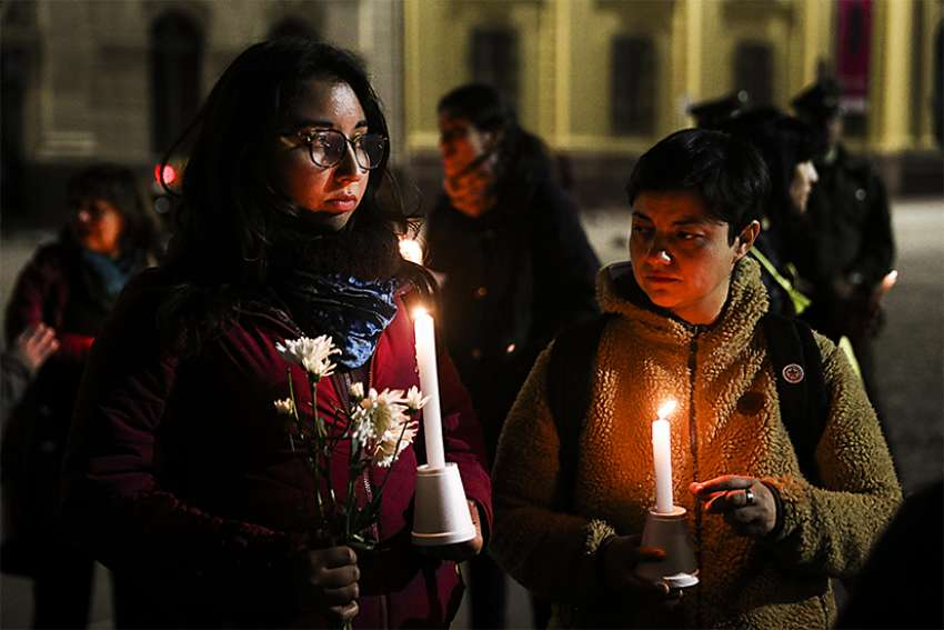 Demonstrators hold candles and flowers Aug. 20 in front of the Metropolitan Cathedral of Santiago, Chile. The demonstration was held as a protest against sexual abuse committed in the Chilean Catholic Church, in an event organized by the Network of Survivors of Ecclesiastical Abuse in Chile.