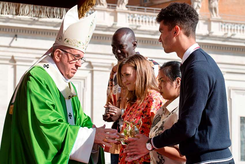 Pope Francis accepts offertory gifts during the opening Mass of the Synod of Bishops on young people, the faith and vocational discernment in St. Peter's Square at the Vatican Oct 3. Among those presenting the gifts was Emilie Callan, a synod delegate from Canada, pictured with the young adults second from left.