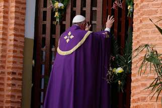 Pope Francis opens the Holy Door at the start of a Mass with priests, religious, catechists and youths at the cathedral in Bangui, Central African Republic, Nov. 29.