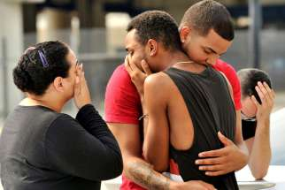 People embrace outside the headquarters of the Orlando, Fla., Police Department June 12 during the investigation of a mass shooting at a gay nightclub in Orlando.