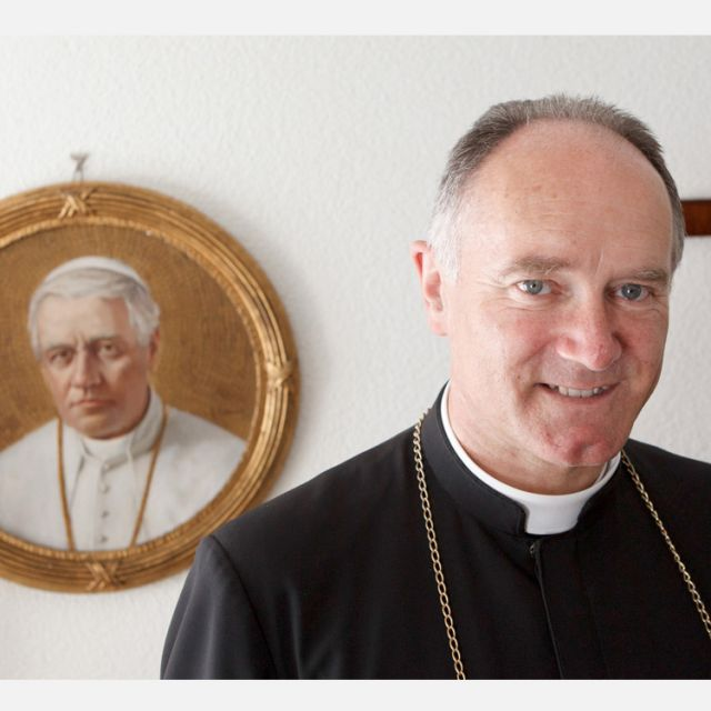 Bishop Bernard Fellay, superior of the Society of St. Pius X, is pictured near an image of St. Pius X at the society's headquarters in Menzingen, Switzerland, May 11.