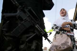 A Filipino woman speaks to a soldier at a checkpoint in Marawi, Philippines, June 1, 2017. Catholic bishops in the southern Philippines supported the declaration of martial law in Mindanao following an attempt by a band of gunmen claiming to be Islamic militants to seize the city.
