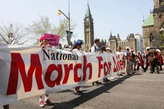 Pro-life supporters carry a banner during the annual National March for Life on Parliament Hill May 2016 in Ottawa, Ontario.