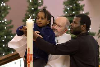 Laken Tchoutouo, 4, lights her sister's baptismal candle with the help of their father, Hypolyte Tchoutouo, and Deacon Simon Nadeau, during a Dec. 9 commemorative Mass at St.-Pierre-aux-Liens Church in Quebec City. Michelle Solaye Mane Tchoutouo, 8, was accidentally killed by a snowplow in Quebec City Dec. 1.
