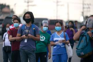 Workers wearing protective masks wait for shuttle services in Manila, Philippines, Aug. 4, 2020, the first day of the government's reimplementation of a stricter pandemic lockdown.