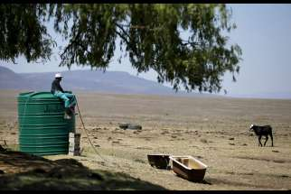 A farmworker sits on a water tank Nov. 9 as he supplies his livestock with water at a drought-stricken farm outside Utrecht, South Africa