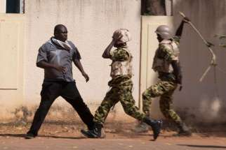 "Soldiers hit an anti-government protester with a stick in Ouagadougou, Burkina Faso, Oct. 30. Burkina Faso's Catholic bishops sent a ""message of peace and hope"" to the West African country after its 27-year president, Blaise Compaore, fled prompting a mi litary takeover."