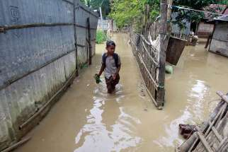 A girl wades through floodwaters near Agartala, India, Sept. 5.