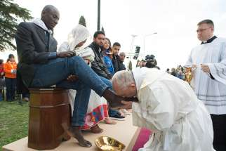 Pope Francis kisses the foot of a refugee during Holy Thursday Mass of the Lord's Supper at the Center for Asylum Seekers in Castelnuovo di Porto, about 15 miles north of Rome March 24, 2016.