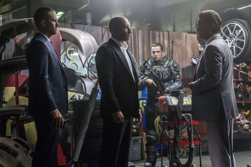Brian (Paul Walker) and Dom (Vin Diesel) meet with a high-level government operative (Kurt Russel) in Furious 7.