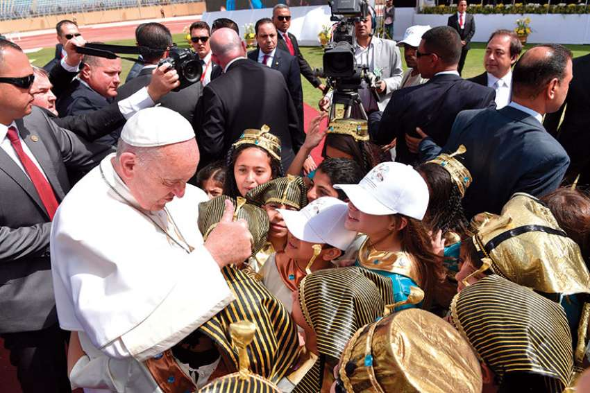 Pope Francis greets children dressed as pharaohs and in traditional dress as he arrives to celebrate Mass at the Air Defense Stadium in Cairo April 29.