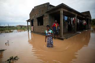 Agiro Cavanda and his wife, Agera, wade through floodwaters outside their home in Pemba, Mozambique, April 29, 2019, in the aftermath of Cyclone Kenneth.