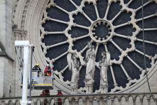 Firefighters inspect one of the rosette windows of Notre Dame Cathedral April 16, 2019, after a fire broke out in the iconic Paris structure. Officials said the cause was not clear, but that the April 15 blaze could be linked to renovation work.
