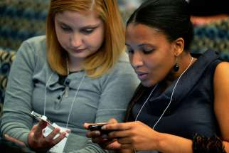 Young women tweet messages during a 2012 conference in Washington. Low-cost video messaging carried across increasingly video-friendly social media platforms will define this year's World Youth Day experience in Krakow, Poland, say several organizations.