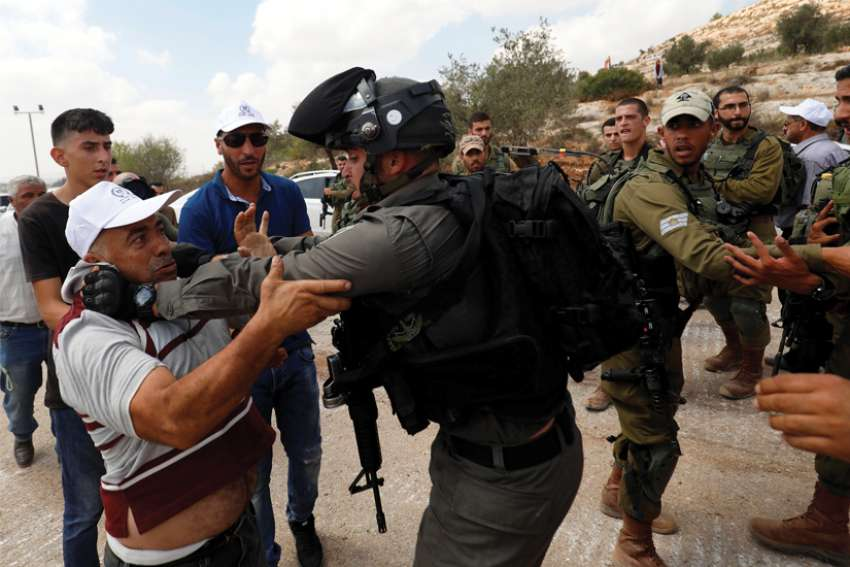 An Israeli border policeman scuffles with a Palestinian man during a protest near Ramallah, West Bank.