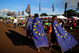 Revellers wrapped in European Union flags walk at Worthy Farm in Somerset during the Glastonbury Festival, Britain, on June 22, 2016.