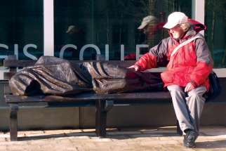 Fr. Peter Larisey has a seat with Homeless Jesus at Regis College.