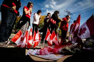 Workers from St. Eugene Catholic School in Hamilton, Ontario, where Cpl. Nathan Cirillo's son is enrolled, pay respects at a makeshift memorial in honor of Cpl. Cirillo, outside the family home in Hamilton Oct. 24. Cirillo was killed during an Oct. 22 s hooting incident at the Canada War Memorial in Ottawa.