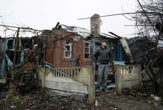 A man stands in front his damaged house after shelling March 24 in the Ukrainian town of Makeevka.
