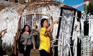 Callie Connors, assistant to local artist Meg Saligman, works to string of prayer intentions on the makeshift walls of the Knotted Grotto outside Philadelphia's Cathedral Basilica of SS. Peter and Paul. Thousands of visitors have added their prayers to the project during the World Meeting of Families 2015.