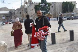 Jasan Zided of Hebron, West Bank, waits to sell Santa hats to tourists in an empty Manger Square Dec. 15 in Bethlehem, West Bank.