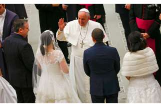 Pope Francis gestures to newlywed couples during his weekly audience in Paul VI hall at the Vatican Jan. 21.
