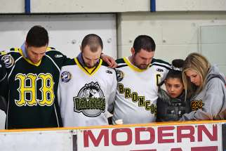 Mourners pray during an April 8 vigil at Elgar Petersen Arena in Humboldt, Saskatchewan, to honor members of the Humboldt Broncos junior hockey team who were killed in a fatal bus accident.