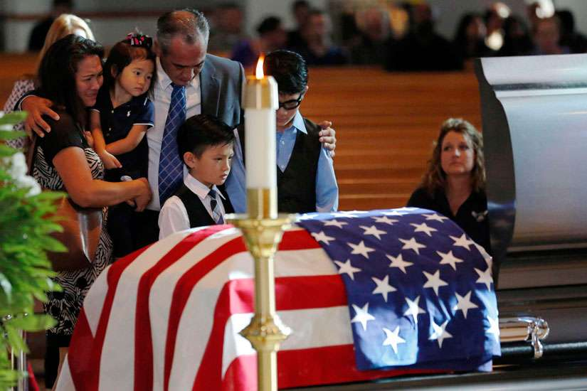Billy Smith, brother of slain Dallas Police Sgt. Michael Smith, and his family grieve at the officer's casket during a July 12 visitation for him at Mary Immaculate Catholic Church in Farmers Branch, Texas. Smith, a member of the parish, was one of five officers killed when a gunman opened fire at a July 7 protest in downtown Dallas.
