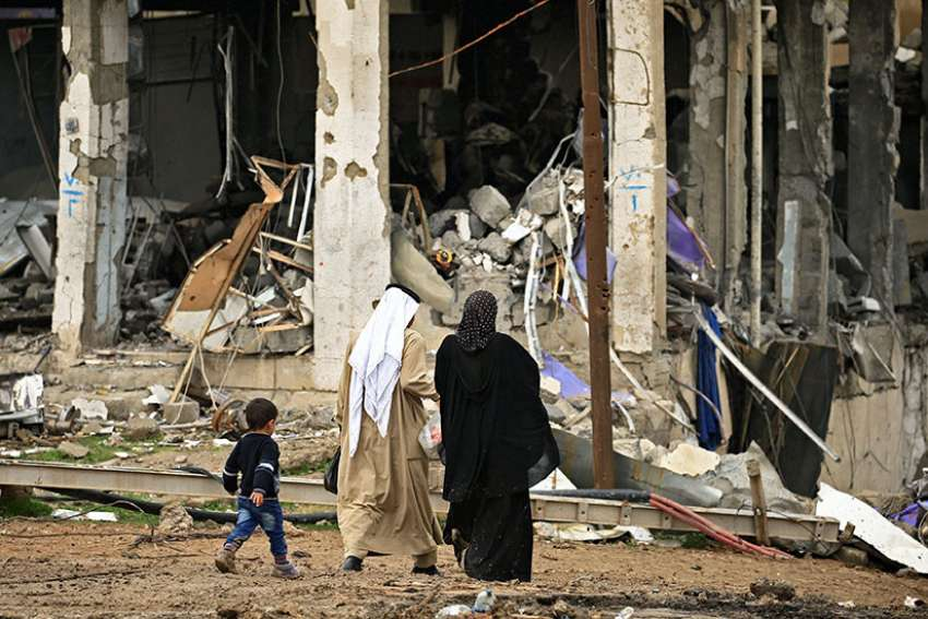 A displaced Iraqi family walks near destroyed buildings March 4 in the Mosul. Iraq was the largest recipient of Aid to the Church in Need's funds in 2016.