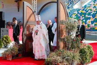 Pope Francis walks through a Holy Door as he arrives to celebrate Mass at Mikheil Meskhi Stadium in Tbilisi, Georgia, Oct. 1.