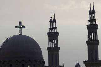 A cross above a church is seen alongside minarets of a mosque April 17 in Cairo ahead of Pope Francis' April 28-29 visit.